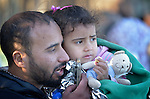 Yalsin Nakasha, a refugee from Daraa, Syria, holds his daughter Zahara, 3, as he uses his mobile phone to inform his family that he arrived safely on the shores of the Greek island of Lesbos just minutes earlier. Along with his wife and two daughters, he is heading for Sweden, and crossed the Aegean Sea in a small overloaded raft.