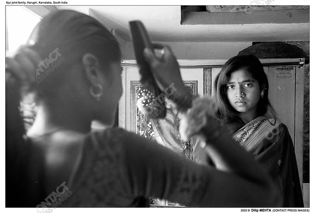 Lakkava (back to the camera, combing her hair) and her cousin dress up for the first time in Saris.