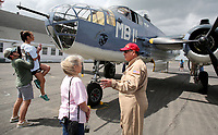 NWA Democrat-Gazette/DAVID GOTTSCHALK  William Barnes (from left) lifts Keeley Dovish Wednesday, April 19, 2017, to look into the nose of a Marine B-25 as Judy Bond listens to Col. Russ Babbitt, Jr., with the Commemorative Air Force of the Southern California Wing, after the plane landed at the Arkansas Air and Military Museum at Drake Field in Fayetteville.The museum is hosting the only airworthy Marine B-25 on the 19th and 20th. The Marine version of the B-25 is designated the PBJ. A donation at the door of $15.00 for adults and $10.00 for children under 12 includes entrance to the museum and a tour of the PBJ.
