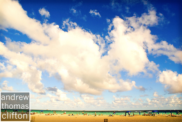 a Sunny day on Miami's South Beach with a cloudy sky, people on the beach, sand, and the ocean