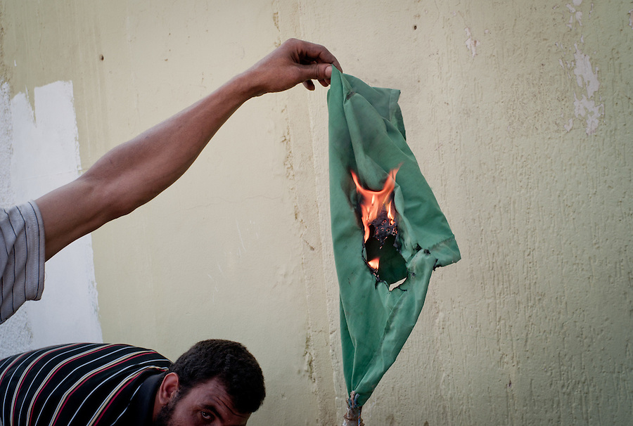 Rebel fighters burn Gaddafi flag in Tripoli, Libya