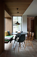 In a contemporary kitchen dining area the walls and ceiling are clad in cedar panelling, which helps to define the area and gives the space an intimate tactile feel. Cushions by Oyuna soften the wood the built-in bench.