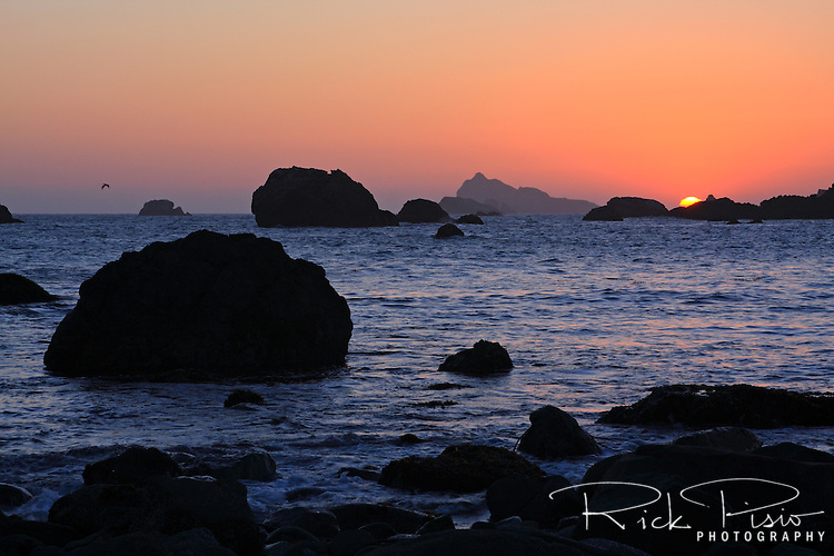 The sun sets over the Pacific Ocean and behind the sea stacks at Battery Point near Crescent City, California.