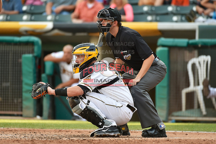John Buck (14) of the Salt Lake Bees behind the plate with home plate umpire Travis Eggert during the game against the Reno Aces in Pacific Coast League action at Smith's Ballpark on July 24, 2014 in Salt Lake City, Utah.  (Stephen Smith/Four Seam Images)