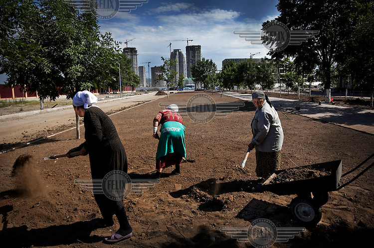 Women do forced labour as ordered by the president, Ramzan Kadyrov. In the distance, new buildings under construction. Everyone has to work a month in the summer without pay to remove all the scars of war, erasing the past and making Grozny a new city.