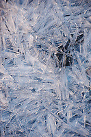 A close-up photograph of ice reveals crystalline patterns in the frozen water.