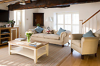 Taking its inspiration from New England the living room is decorated in shates of white, cream, red and blue with a large sofa and armchair upholstered in beige linen