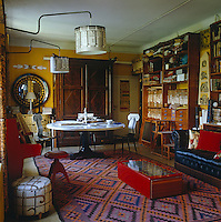 The living room is furnished with various Piero Fornasetti pieces and the shelves are filled with his design books and fabric samples
