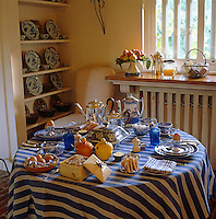 A blue and white mattress ticking covers the round table which is laid for breakfast with blue and white Spode plates, a honeycomb and eggs from the local farm