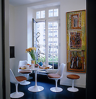 In the kitchen-diner the Tulip table and chairs are arranged next to a large window with a decorative wrought-iron grille, open to catch any available breeze in the hot city summer; the painting on the adjacent wall is by New Orleans artist Charles Young