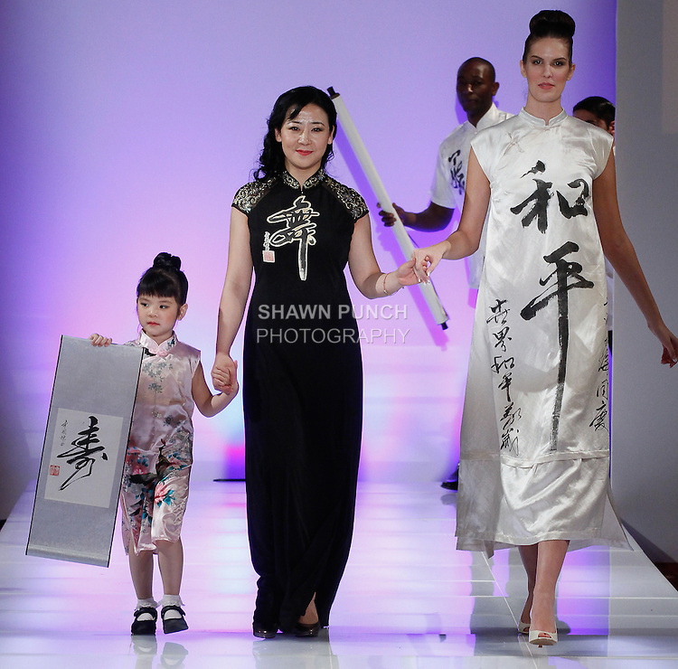 Chinese fashion designer YiLing Li walks runway with models for the close of her YiLing Li fashion show, during Couture Fashion Week Fall 2014, on February 16, 2014.