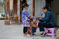 An elderly woman of the ethnic Bouyei Tribe helps her grandchild put on a traditional headdress at Wangmo County in China's southwestern Guizhou Province, April 2019.