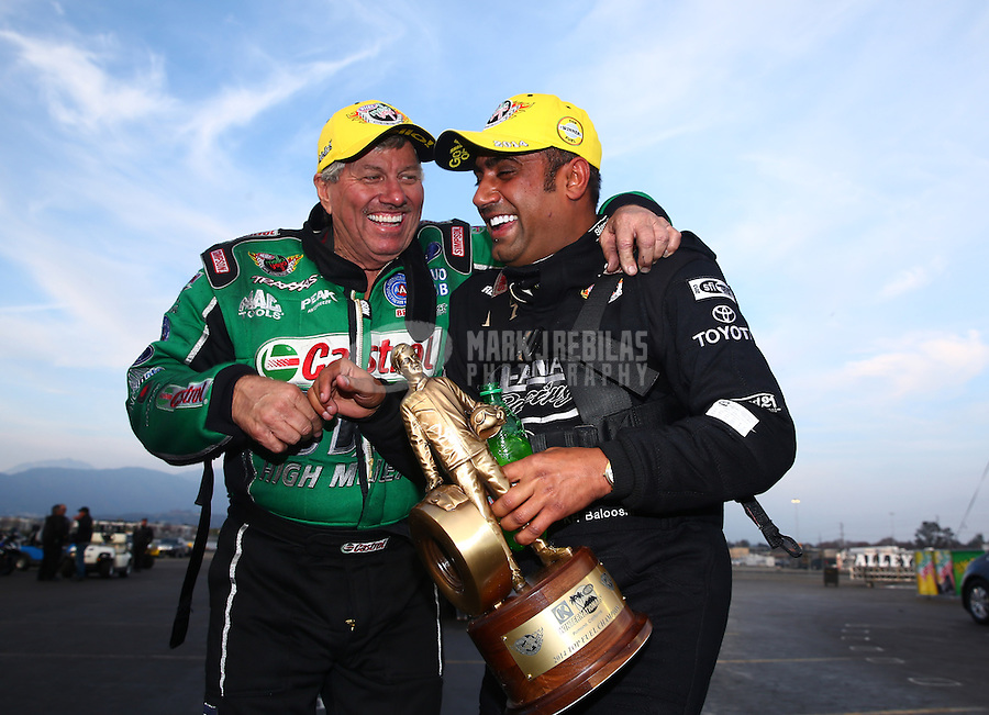 Feb 9, 2014; Pomona, CA, USA; NHRA top fuel dragster driver Khalid Albalooshi (right) celebrates with funny car driver John Force after winning the Winternationals at Auto Club Raceway at Pomona. Mandatory Credit: Mark J. Rebilas-