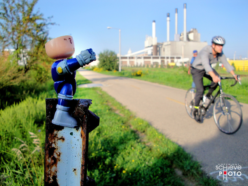 An action figure salutes as bikers pass by.