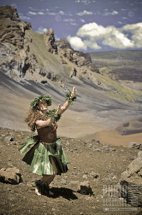 Native woman dancing hula with ipu (gourd) at Haleakala crater, island of Maui