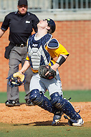 Canisius Golden Griffins catcher Christ Conley (13) tracks a foul pop fly during the game against the Charlotte 49ers at Hayes Stadium on February 23, 2014 in Charlotte, North Carolina.  The Golden Griffins defeated the 49ers 10-1.  (Brian Westerholt/Four Seam Images)