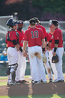 Kannapolis Intimidators pitching coach Jose Bautista (38) leads a meeting on the mound during the game against the Hickory Crawdads at CMC-Northeast Stadium on May 21, 2015 in Kannapolis, North Carolina.  The Intimidators defeated the Crawdads 2-0 in game one of a double-header.  (Brian Westerholt/Four Seam Images)