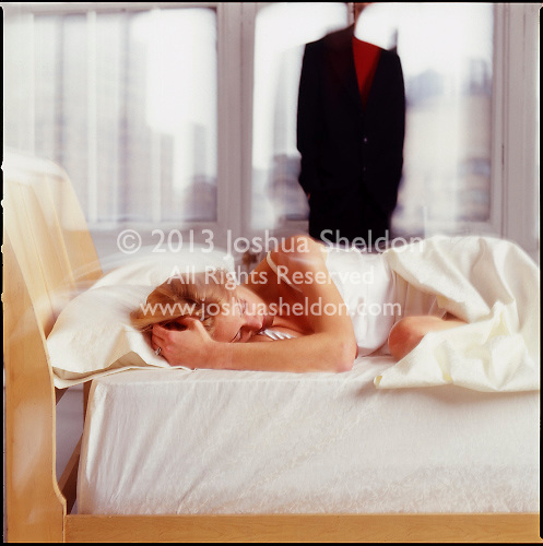 Woman in bed with man in background