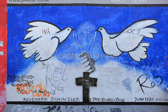 Section of the Berlin Wall depicting a painting by Rosemarie Schinzler entitled Alles Offen, with 2 doves lifting the Brandenburg Gate and a cross, damaged by graffiti, part of the East Side Gallery, a 1.3km long section of the Wall on Muhlenstrasse painted in 1990 on its Eastern side by 105 artists from around the world, Berlin, Germany. Picture by Manuel Cohen