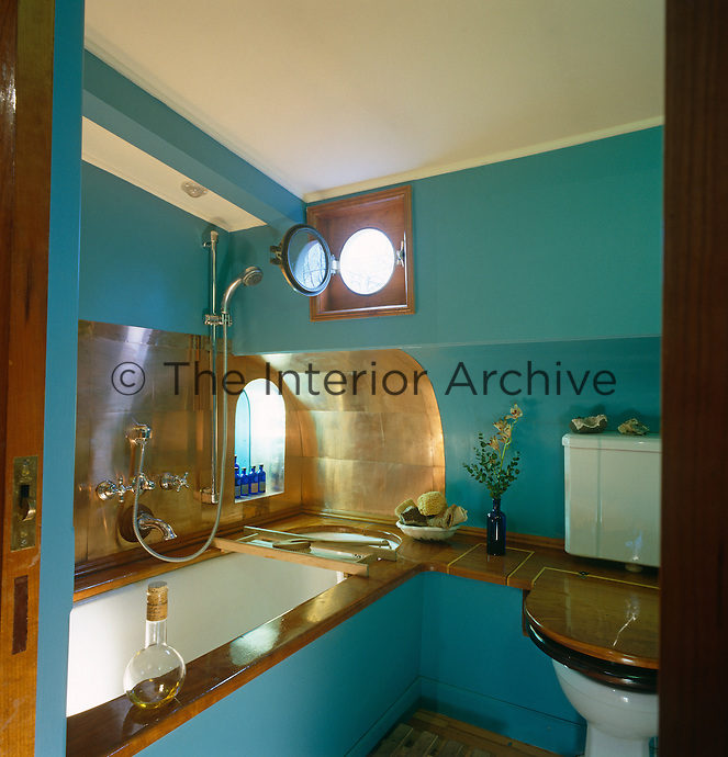 Compact bathroom with porthole on a houseboat moored on the Thames