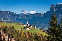 Italy, Alto Adige - Trentino (South Tyrol), Renon: view across the earth pyramides (Hoodoos), village Monte di Mezzo with church St. Nikolaus (built 1200) towards the Dolomites with Sassolungo (Langkofel), Sasso Piatto (Plattkofel) and Sciliar (Schlern) mountains   Italien, Suedtirol (Alto Adige-Trentino), Ritten: Blick ueber die Erdpyramiden und Mittelberg am Ritten mit der St. Nikolauskirche (erbaut um 1200) in die Dolomiten mit Langkofel, Plattkofel und dem Schlern (rechts)