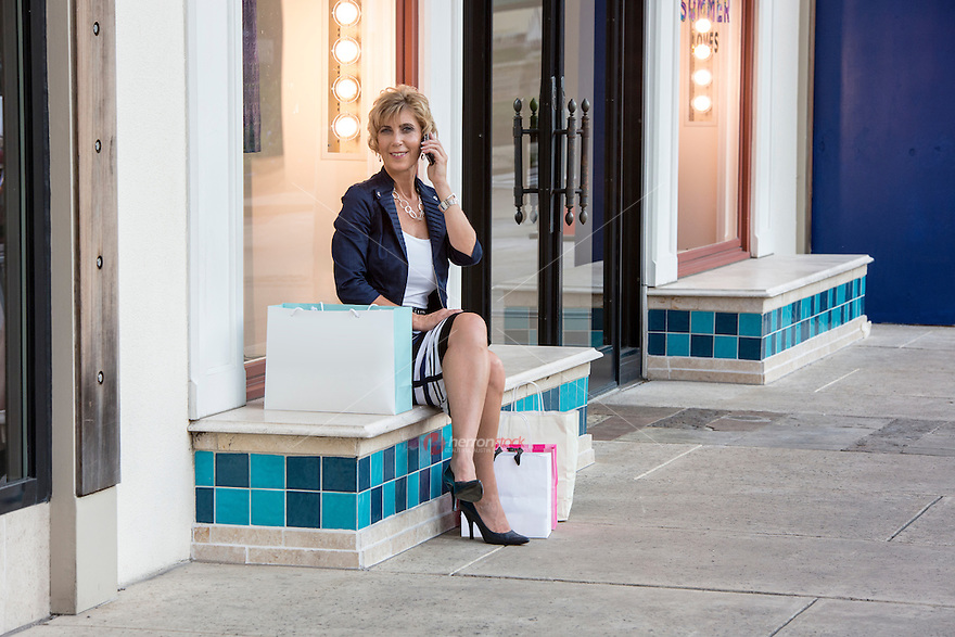 Shopping. A beautiful blonde business woman with shopping bags talking on a smart phone in a Austin shopping center in Austin, Texas.