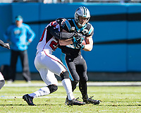 CHARLOTTE, NC - NOVEMBER 17: Christian McCaffrey #22 of the Carolina Panthers is tackled by Kendall Sheffield #20 of the Atlanta Falcons during a game between Atlanta Falcons and Carolina Panthers at Bank of America Stadium on November 17, 2019 in Charlotte, North Carolina.