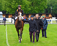 Winner of The DEOS Group Handicap Loving Your Work (14) ridden by Kieran O'Neil and trained by Ken Cunningham-Brown is led into the Winners enclosure during Evening Racing at Salisbury Racecourse on 11th June 2019