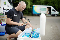 bidons being kept cool by hammering the ice out of a frozen bottle<br /> <br /> Tour de France 2014