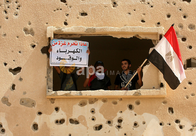 """Palestinians wave a national flag and an Egyptian flag as they take part in a rally calling on Egyptian authorities to open the Rafah crossing, outside the crossing in the southern Gaza Strip September 16, 2013. Cairo closed the Rafah crossing, Gaza's main window to the world, completely last week after assailants crashed two explosive-laden cars into a security building adjacent to the border zone, killing six Egyptian soldiers. Ashraf al-Qidra, spokesman for the Hamas-run Gaza Health Ministry, said 1,000 patients a month required medical care in Egypt and in other countries. Rafah's closure, he said, would also affect the import of medication and prevent foreign doctors from visiting Gaza. The signs read, """"We Gaza is deprived of power and fuel"""" (L) and """"We demand the Egyptian side to find alternatives for the closure of tunnels. Photo by Eyad Al Baba"""