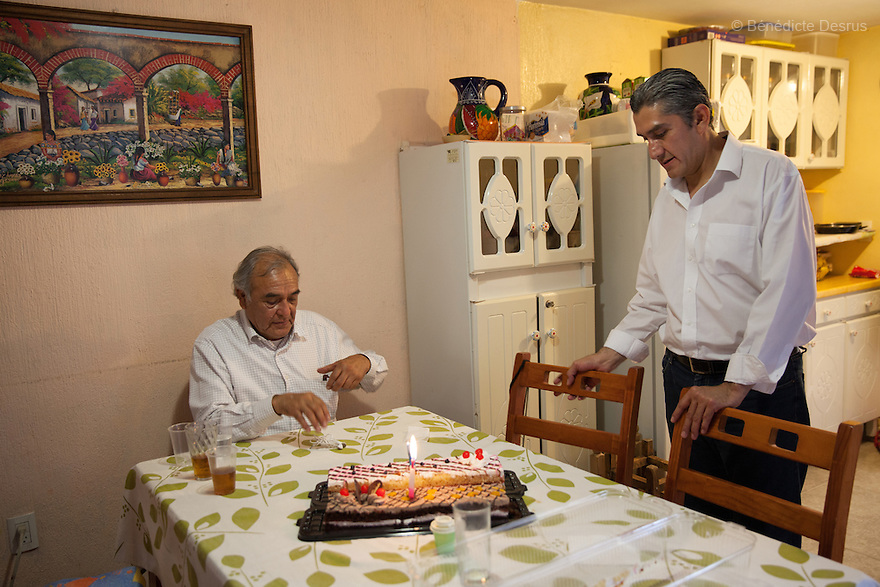 """Donovan (R), pictured with his father (L), while celebrating his 43rd birthday with his family at his home in Texcoco, Mexico on May 9, 2015. Donovan Tavera, 43, is the director of """"Limpieza Forense México"""", the country's first and so far the only government-accredited forensic cleaning company. Since 2000, Tavera, a self-taught forensic technician, and his family have offered services to clean up homicides, unattended death, suicides, the homes of compulsive hoarders and houses destroyed by fire or flooding. Despite rising violence that has left 70,000 people dead and 23,000 disappeared since 2006, Mexico has only one certified forensic cleaner. As a consequence, the biological hazards associated with crime scenes are going unchecked all around the country. Photo by Bénédicte Desrus"""