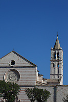 A quite classical view of the high part of the façade of Santa Chiara church in Assisi, with its bell-tower on the right, between the green trees in the place in front of it, among which appear in particular the two small marble lions on the two main door sides. Digitally Improved Photo.
