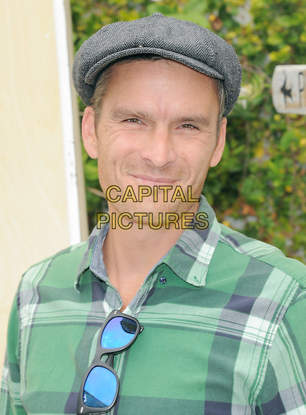 """Balthazar Getty .Book Party For """"Last Night I Swam With A Mermaid"""" Held at Annenberg Community Beach House in Santa Monica, California, USA..April 22nd, 2012                                                                                .headshot portrait green check shirt flat cap hat  .CAP/RKE/DVS.©DVS/RockinExposures/Capital Pictures."""