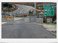 Concrete blocks and a massive metal gate block the exit of the Palestinian village of al-Tira  to Road No. 443. Road 443 is one of the main throughways of the West Bank. Its overall length is 25.5 KM, 14 out of which run through the heart of the West Bank. .With the break of the second Intifada at the end of 2000, Israel had severely restricted Palestinian movement on road 443, which was their main road from the Beit Sira, Saffa, Beit Liqiya, Kharbatha al-Misbah, Beit Ur al-Tahata, Beit Ur al-Foqqa and al-Tira villages to Ramallah. These restrictions were harshened in 2002, when Palestinian movement was completely prohibited. In recent years all entries and exits from the road to the area's villages were blocked with gates and concrete slabs. Photo by Quique Kierszenbaum