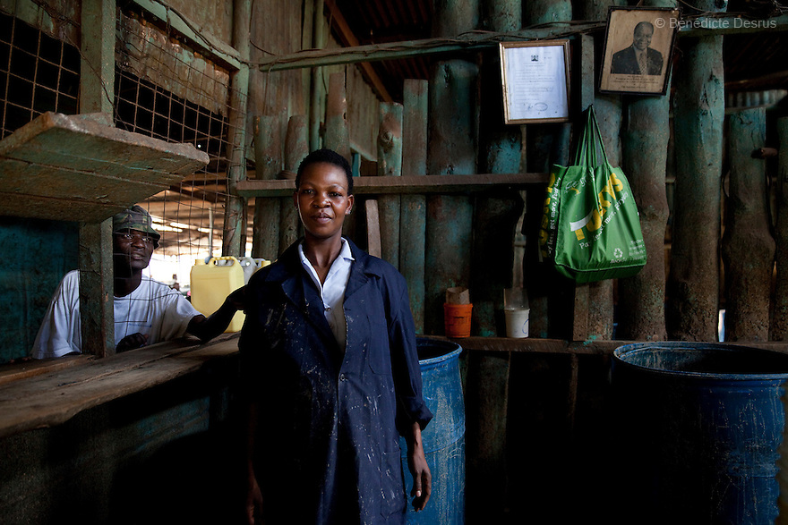 Alice Mutuwa working at the Madiaba Busaa Club in a Nairobi slum on March 27, 2013. Alice has been selling Busaa, a traditional fermented beer, for more than 10 years at the Madiaba Busaa Club. Busaa is made by crudely fermenting maize, millet, sorghum or molasses. At Kshs 35 per liter it is much cheaper than a Kshs120 half-liter bottle of commercial beer. The local brew was legalised in 2010 and since then busaa clubs have become increasingly popular. Drinking is on the rise in Kenya, especially among young people. Photo: Benedicte Desrus