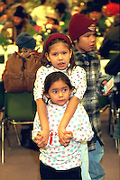 Sisters holding hands at soup kitchen Christmas dinner age 4 and 6.  Minneapolis  Minnesota USA