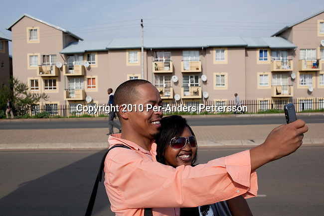 SOWETO,SOUTH AFRICA - JANUARY15: Ayoung couple takes pictures of themselvesin front of a newly constructed security complexonJanuary15, 2010,inthe Kliptown section ofSoweto, South Africa.Soweto is the largest township in South Africa, located about 10 kilometers southwest of downtown Johannesburg. The population is estimated to be around 2-3 million.A growing black middle class can be seen in the township and many shopping malls and has been built the last few years.(Photo by Per-Anders Pettersson/Getty Images)