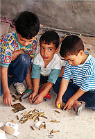 Young Palestinian boys play with used Israeli  army bulets on the roof of their downtown Hebron home July 14, 97, used by Israeli troops as a sniping post against Palestinian rioters. Photo by Quique Kierszenbaum, ©Quique Kierszenbaum