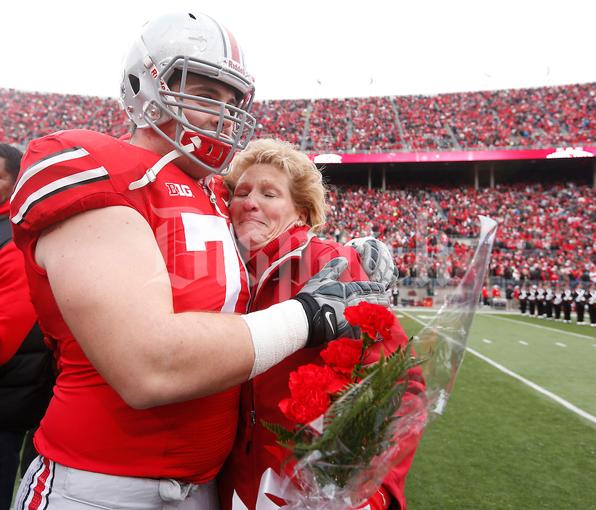 Ohio State Buckeyes offensive linesman Corey Linsley (71) embraces family as nineteen seniors were recognized before Saturday's NCAA Division I football game against Indiana at Ohio Stadium in Columbus on November 23, 2013. (Barbara J. Perenic/The Columbus Dispatch)