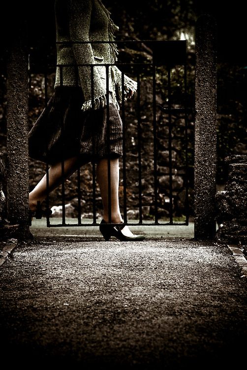 woman walking past metal gate