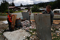 Shirley Ecklund is taking apart a house in town to salvage the wood for a new deck on their float house.  She works with her sons JJ Beesley (short hair) and Marcus Lee (longer hair) taking out nails.  Swede and Shirley Ecklund have lived 12 years in a  float house where transportation is only by boat or float plane.  They have cherry, maple and other trees as well as many other plants.  They are known as gourmet cooks and have an unofficial restaurant.  People stop by almost daily for meals. They used to cook for logging camps but have had many other lives. Swede was a professional boxer..Now he is the president of the school board.  Swede & Shirley take in foster boys - only kids who have gotten in trouble with the law, and would otherwise go into a detention home..They live on Piggy Cove--named for a pot belly pig for 12 years (t died this winter) and now they have a dog named Meatball.