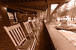 NEW PALTZ - MARCH 13: Rocking Chairs on Lakeside Balcony of historic Mohonk Mountain House, monochrome sepia. Wide angle horizontal view, with glimpse of frozen lake, distant small gazebo on one side and stone arched walkways and green and stone exterior of the inn on other side, on winter morning of March 13, 2010 at New Paltz, New York, USA. For Editorial Use Only.