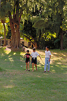 Three children walk through a lush green park.