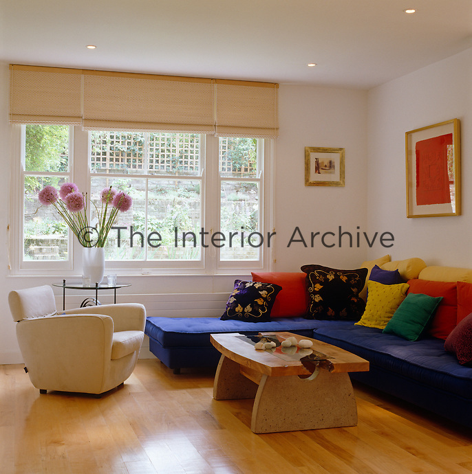 An L-shaped sofa is covered with colourful scatter cushions in this simply furnished family room