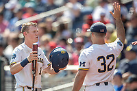 Michigan Wolverines first baseman Jimmy Kerr (15) is greeted by teammate Joe Pace (32) during Game 11 of the NCAA College World Series against the Texas Tech Red Raiders on June 21, 2019 at TD Ameritrade Park in Omaha, Nebraska. Michigan defeated Texas Tech 15-3 and is headed to the CWS Finals. (Andrew Woolley/Four Seam Images)