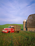 Whitman County, WA<br /> Vintage red Ford flatbed truck parked in front of a weathered barn and silo in summer
