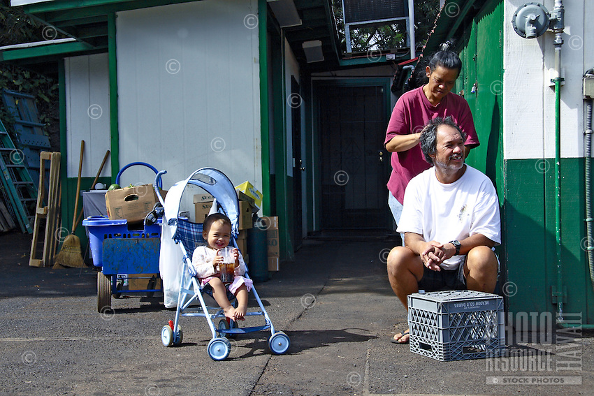 A dad gets a haircut from mom with baby watching during a break from work at Polli's Mexican restaurant in the upcountry town of Makawao.