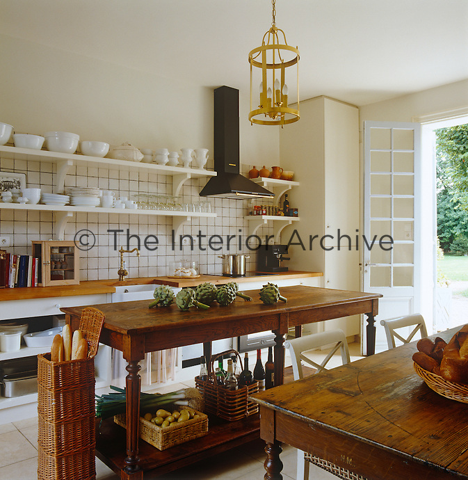 A vintage French worktable is used as an island in the tiled kitchen while open shelves display a collection of French porcelain