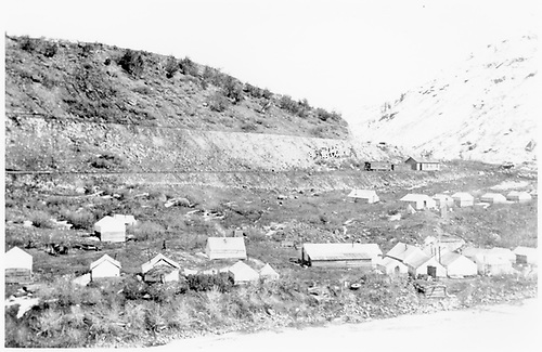 Construction camp or early town on slope between river and railroad embankment on hillside.  Tent buildings and log shanty.  Railroad station, passenger car and box car on railroad level.<br /> D&amp;RG  Somerset, CO  ca 1902