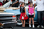 "Sisters Lola Facha, 8, center, and Reese Facha, 6, right, watch classic cars cruise the streets of Modesto, California during the American Graffiti Parade, June 7, 2013. Modesto is celebrating the 40th anniversary of the film ""American Graffiti"", with a parade headed up by native son, filmmaker George Lucas."